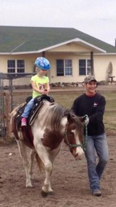 Vision, a blind paint pony, is lead around  as a little girl rides.  Photo courtesy of White Horse Ranch
