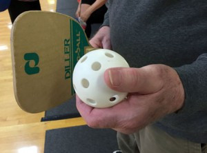 Jack Schuh holds a perforated plastic baseball, used to play pickleball. Photo by Frank Lee