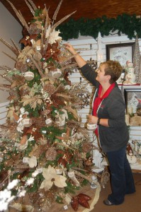 Store clerk Diane Wildung finishes decorating a tree in the holiday gift room. Photo by Scott Thoma