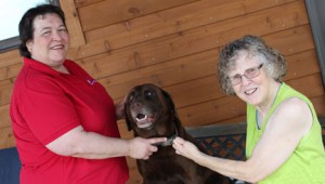 Brain injury survivors Sharon Gieseke, left, director of Minnesota Brain Injury Force Inc., and Sandy Lund, right, share a moment with Gieseke's family dog, Rufus, also a brain injury survivor after someone shot him in the head with a gun four years ago. Photo by Steve Palmer