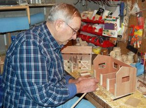 Wally working on a stable in his workshop. A completed stable is to the left of the one he is working on. Photo by Scott Thoma