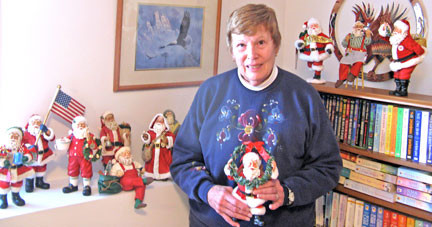 Sonje Zeitler is shown with only a few of her Santas by Possible Dreams. The collection started in the 1990s, and she now has approximately 60 of the Clothtique Santas that were given as gifts. It's a labor of love when they are unwrapped each year and set around the family room. Photo by Jennie Zeitler