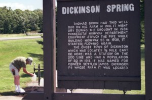 Chelsea Caye of Greenfield fills a couple of gallon jugs with free drinking water at Dickinson Spring while a large wooden sign in the foreground relates a brief history of the continually flowing artesian well along Minnesota Highway 55 between Buffalo and Rockford.