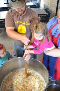 Wollak's grandchildren help stir bouja at this year's feed. Contributed photo