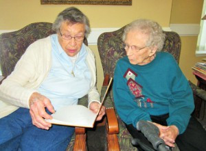 Marie Dietel and Malinda Stoeckmann read a book together at The Harbor at Peace Village in Norwood Young America. Photo by Cathy Nelson