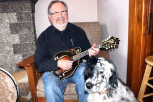 Dick Kimmel plays the mandolin for his dog Corbett who is featured on the cover of his recently released CD, Corbett On the Couch. Photo by Steve Palmer