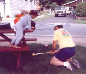 Kids watch as one of the participants hits a ball under the picnic table during the tournament in 1991. The croquet courses are never the same and tend to get more challenging for the finals. Lakes, roads, sidewalks, tree roots and picnic tables often add to the challenge of the games. Contributed photo.