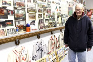 "Donald ""Duke"" Cook with part of the museum collection of regional amateur baseball and major league exhibits plus softball team memorabilia located in a former school building at Leavenworth."