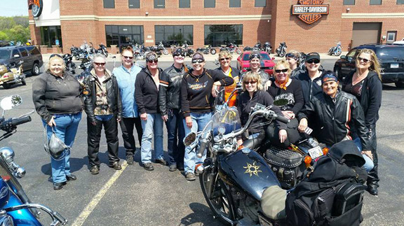 The International Sewing Club took this group photo in front of a Harley dealership at a stop in one of their rides. The group has been riding motorcycles together since 1993. Contributed photo