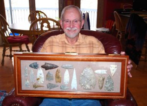 Mike Trekell holds a case with a variety of arrowheads and knives that are worth thousands of dollars and are presently being sold at auction. Note the largest one, a ceremonial blade. Photo by Bill Vossler