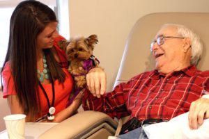 Brittney Odens, marketing coordinator at Rice Memorial Hospital, is also one of the handlers in the volunteer pet therapy program offered by Rice Hospice. Here she is with her yorkie, Maggie, bringing a smile and comfort to a patient. Contributed photo