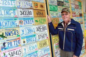 Everett Hanson, 88, stands next to part of his 400 plus license plate collection, which he neatly displays on several portable hinged plywood panels for viewing.