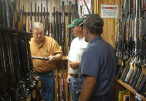 Jim Condon, owner of Little Crow Shooting Sports for 29 years, takes pride in the service they provide their customers. Above, Condon helps a couple customers with questions on a particular gun. Photo by Scott Thoma