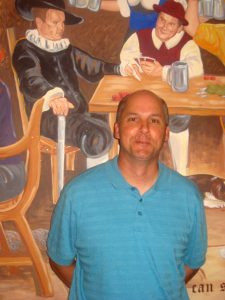Bowling alley owner Steve Bates stands in front of the new mural in his banquet room. Photo by Jean Paschke
