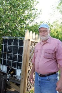 Ken Hovet, of rural Browerville, stands next to the watering system that supplies his bucket garden.  Photo by Nancy Leasman