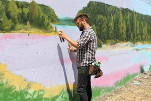 "Artist Michael Cimino spray paints the ""Dawn"" section of the 540-foot long Mankato Flood Wall Mural project featuring the Minnesota River.  The mural was painted during the month of July by five artists that attracted a number of onlookers who stopped to take photos and watch the artists work on the large outdoor canvas.  Photo by Steve Palmer"