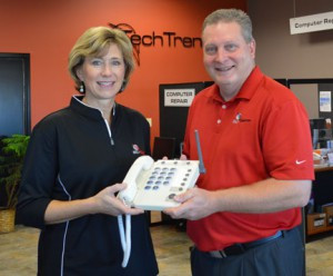 Kathy VanRoekel and Darrin Meendering, of NU-Telecom, with one of the Care Call handsets NU-Telecom offers