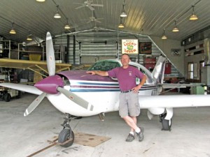 "Dennis Kahlhamer is pictured next to his plane in the ""Lucky 'Leven"" hangar at the Little Falls Airport. The hangar is outfitted with a kitchen (lacking only running water) and hosts a gathering of pilots and families once a month during the summer months.Photo by Jennie Zeitler"