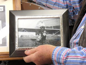 Wilbur holds a photo of his dad when his dad built a plane in 1928. Photo by Bev Ahlquist