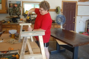 Deb Thorpe uses a drill on a bench she is making. Thorpe has been making all sorts of things out of wood over the last few years after her husband, Duane, passed away. Photo by Scott Thoma