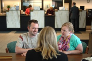 Stacey Pederson, customer service, helps a young couple at  Eagle Bank in Glenwood. Eagle Bank has been helping customers in west central Minnesota for more than 100 years.  Photo by Jim Palmer.