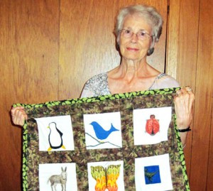 Evelyn Christensen with one of her custom quilts. Photo by Karen Flaten