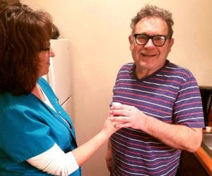 A CompassionCare client is helped with medication. Contributed Photo