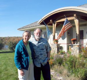 Sue and Van Gooch by their zero-energy home on Echo Lake near Alexandria. The home cost about 30 percent more to build than a typical home, but they are getting that money by in energy savings.  Photo by Carol Stender