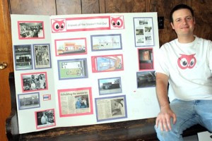 Jim Pessek sits next to a display board with the history of the Stewart Red Owl store and an artist's conception of what the renovated interior of the vacant building could look like once renovation is completed.          Photo by Steve Palmer