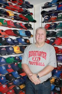 Brad Koenig stands next to shelves that display his collection of over 700 caps from all professional and college sports teams. Photo by Steve Palmer