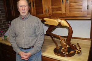 """Walter stands next to a unique large wooden crane-like bird named """"Igor."""" He made the bird in his wood shop and won a Grand Champion ribbon at the Sibley County Fair. Photo by Steve Palmer"""