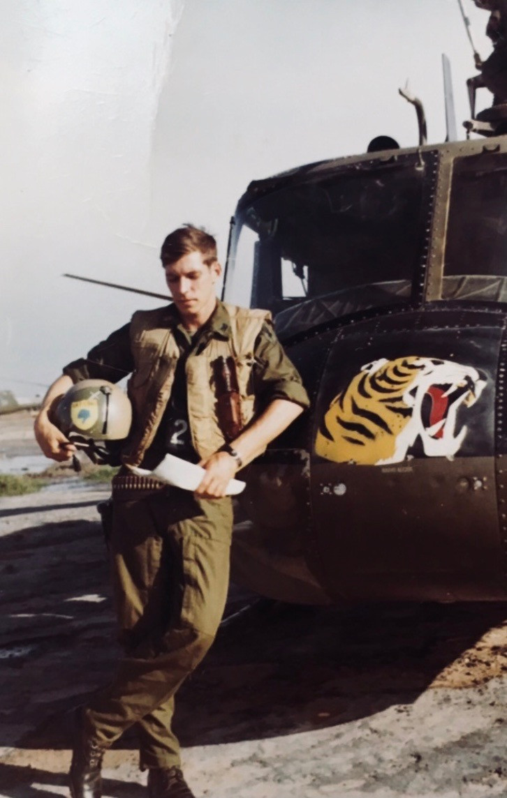 Captain Scott Alwin poses with huey helicopter bearing Top Tiger emblem