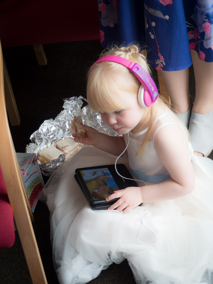 Flower girl catching up on a video and having a sandwich during the ceremony