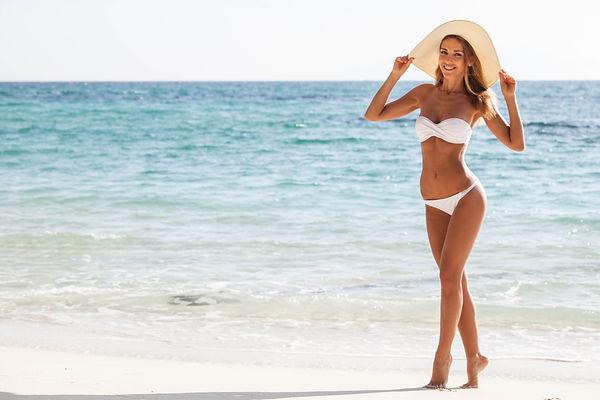 Happy smiling woman in bikini and sunhat