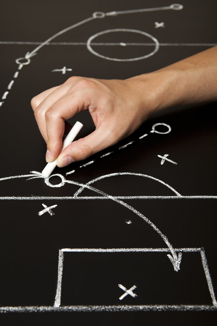 Hand drawing a soccer game strategy with