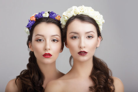 Fashion editortial photography: Two young women with gorgeous makeup and stylish hair with floral decorations.