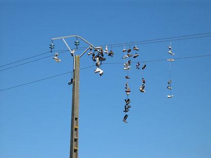 Une multitude de chaussures suspendues à un fil électrique