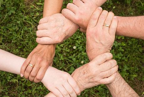 cinq personnes se tiennent les mains en cercle pour exprimer la cohésion