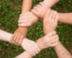 des personnes forment un lien avc leurs mains pour montrer la cohésion