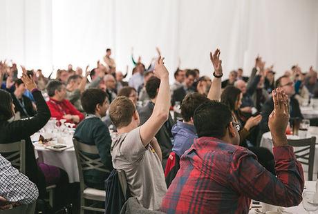des personnes lèvent la main lors d'un séminaire