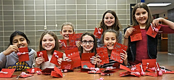 Girl Scouts decorating Valentine cards for foster kids.