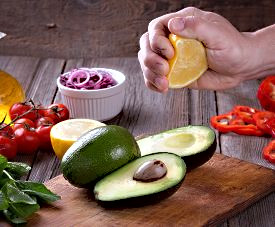 man_hand_squeezing_lemon_avocado_guacamo