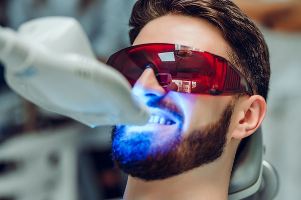 Man having teeth whitening by dental UV