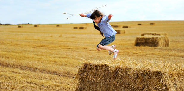 Girl jumping off hay bale