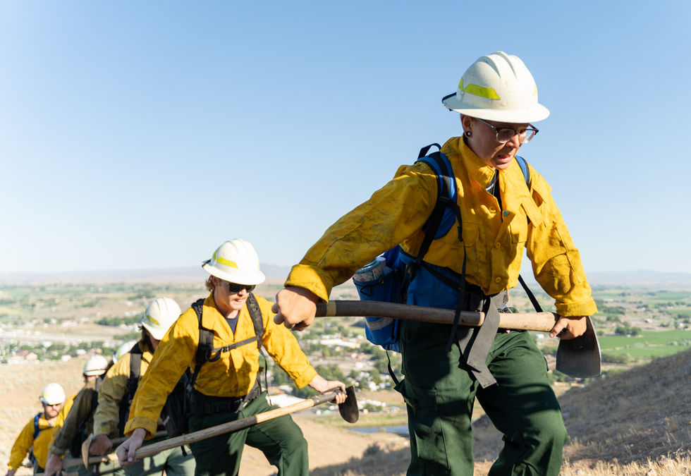 """Darla Allen, a recruit from Houston, Tex., hikes with the rest of the engine crew during a training routine. Each morning at 8 a.m., the team engages in physical training of some variety. On the morning of June 24, this training involved an intensive hike up Vale's Rinehart Butte, which has an elevation of approximately 3,000 feet. They had to come prepared """"in packs and yellows,"""" meaning they had to hike with all of the equipment they would normally carry at a fire. Between fireproof clothes and a helmet, heavy packs that include a fire shelter and water, and their hand tool, the engine crew members might be carrying 40-55 pounds or more. """"How we feeling?"""" the leader of the group said to the trainees once they reached the top of the butte. """"Peachy,"""" replied Allen."""