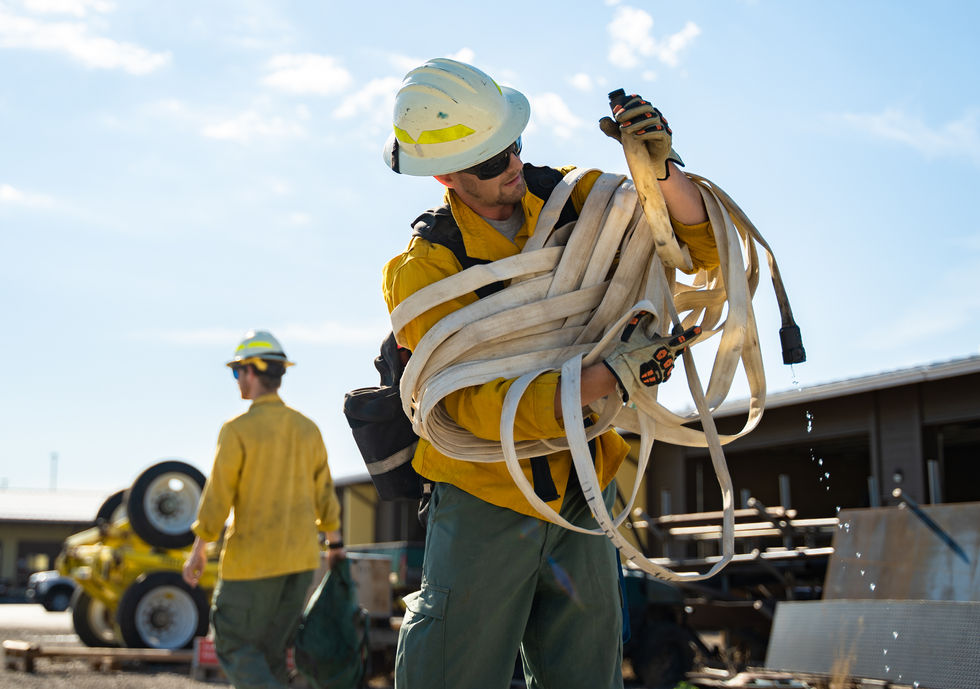 """Nathan Manser uses the butterfly method to wrap the hose up after the engine rodeo's hoselay training exercise where trainees had to extend the hose from the engine to the imaginary fire without interrupting the hydraulics. """"Some call me Michael Phelps,"""" he jested."""