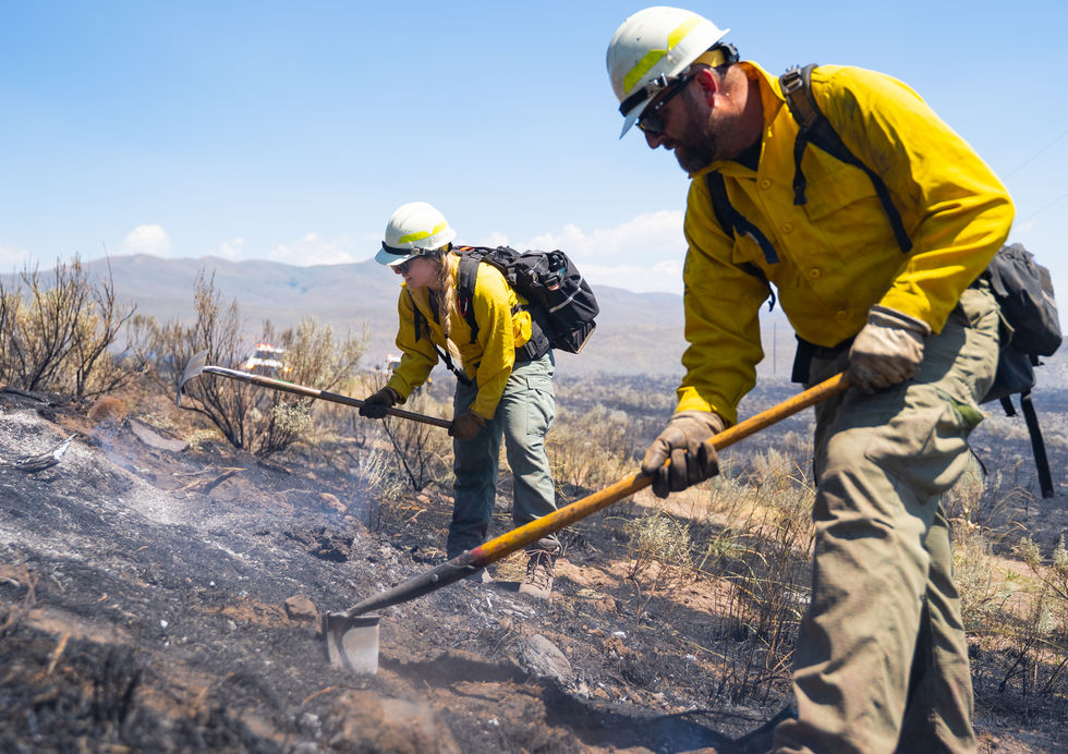 Robyn Mitton (left) and engine captain Justin Fenton chat together as they extinguish lingering flames and embers with their tools at the edge of the Miller Flats fire. The fire swept through private land near Ironside, Ore. on July 7, 2021. One of the first notable fires of the season, the trainees could finally put their skills to the test in the field.