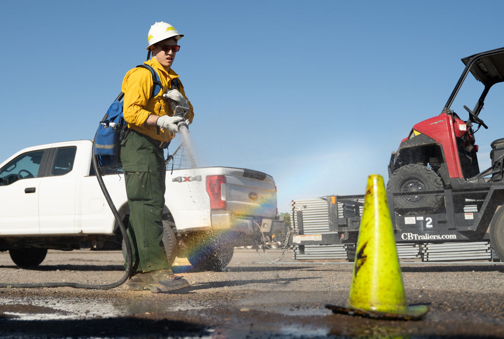 Cooper Besougloff from Virginia sprays a cone placed to simulate a fire line at the engine rodeo on July 1, 2021.