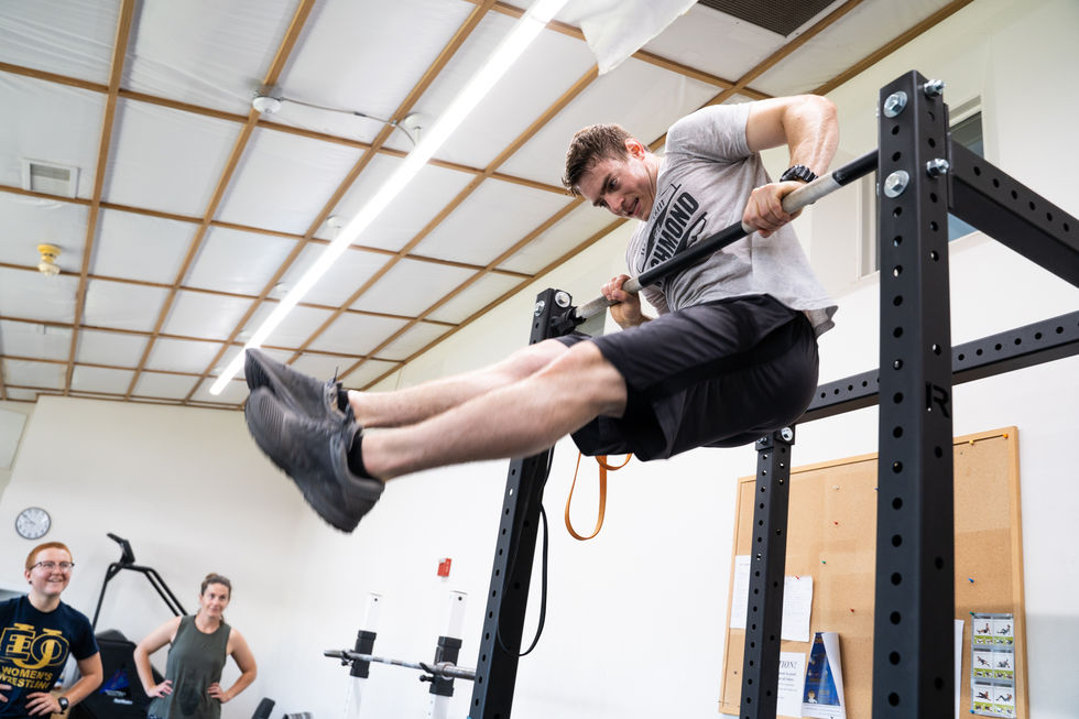 """Besougloff impresses the crowd, including recruits Darla Allen (left) and Danielle Kona (right) with a muscle-up. """"He's a beast,"""" Connelly Schlupe, a well-seasoned 23-year-old fighter said."""