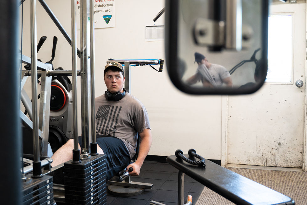 """Aidan Aman, an 18-year-old first-time firefighter, uses the leg press in the on-site gym at the Vale District BLM on June 23, 2021. The gym is well-stocked with a variety of machinery and weights, and most of the 8 a.m. physical trainings take place there. Cooper Besougloff (pictured in reflection) said, """"Physical fitness and training is so important in this field, so [the higher-ups] put a lot of emphasis on it."""""""